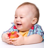 Little child is eating red apple and smile Stock Photography