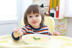 Little child eating vegetable cream soup. Healthy nutrition Stock Images