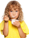Little child eating yogurt Royalty Free Stock Photography