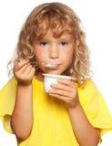 Little child eating yogurt. On white Royalty Free Stock Photography