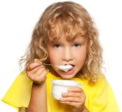 Little kid eating yogurt. Child. Little child eating yogurt on white Stock Photography