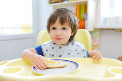 Little child eats cheesecake Stock Photo