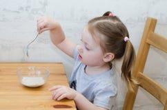 Little child eats his tasty porridge. Little girl stirs porridge with a little spoon stock photos