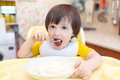 Little child eats quark with sour cream on kitchen Royalty Free Stock Photography