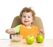 Little child eats with spoon sitting at table with Stock Photos