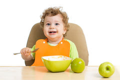 Little child eats with spoon sitting at table with Stock Photo