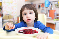 Little child eats tasty red soup Royalty Free Stock Photo