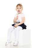 Little child eats yogurt. Little baby girl with spoon eats yogurt on a white background Royalty Free Stock Photos