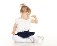 Little child eats yogurt. Little baby girl with spoon eats yogurt on a white background Stock Photography
