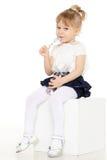 Little child eats yogurt. Little baby girl with spoon eats yogurt on a white background Royalty Free Stock Image