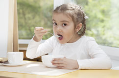 Little child eats yogurt Stock Photos
