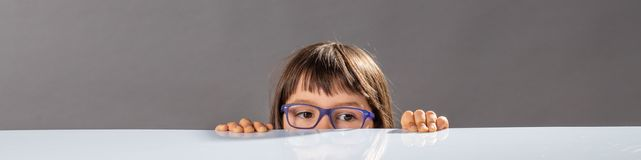 Little child with eyeglasses hiding, too small to reach out. Shy little child with eyeglasses hiding half of her face below a table, being too small to reach out Stock Photography