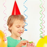 Little child in festive hat eating piece of birthday cake Royalty Free Stock Photo