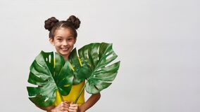 Free Little Child Girl 9 Years Old In Yellow Dress With Big Leaves Monstera In Hands Stock Image - 192108231