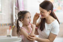 Little child girl brushing teeth in bath Stock Image