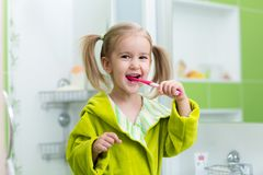 Little child girl brushing teeth in bath royalty free stock image
