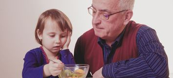 Little child girl does not want to eat and has no appetite. Grandpa feeding his grandchild with fruits salad