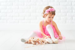 Little child girl dreams of becoming  ballerina with ballet shoe Royalty Free Stock Photos