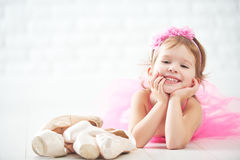 Little child girl dreams of becoming  ballerina with ballet shoe Stock Images