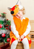 Little child girl dressed in fox suit near Christmas tree. Royalty Free Stock Photo