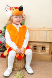 Little child girl dressed in fox suit near Christmas tree. Royalty Free Stock Image