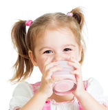 Little child girl drinking yogurt or kefir. Isolated on white background Royalty Free Stock Photos