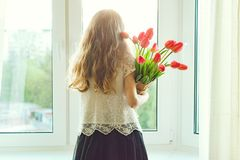 Little child girl holding bouquet of red tulips royalty free stock images