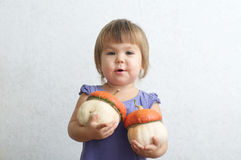 Little child girl holding two decorative pumpkins Royalty Free Stock Photography