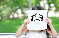 Little child girl holding up a white paper with draw crying face expression in nature park.  royalty free stock photos