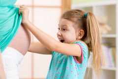 Little child girl looking at mother pregnant tummy Royalty Free Stock Photo