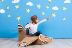 Little child girl in a pilot`s costume is playing and dreaming of flying over the clouds. Royalty Free Stock Photos