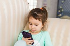 Little child girl play on smartphone at home royalty free stock photos