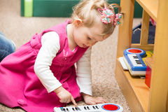 Little child girl playing in kindergarten in Montessori Class. Royalty Free Stock Images