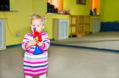 Little child girl playing in kindergarten in Montessori preschool Class. Adorable kid in nursery room. Royalty Free Stock Image