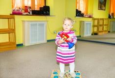 Little child girl playing in kindergarten in Montessori preschool Class. Adorable kid in nursery room. Royalty Free Stock Images