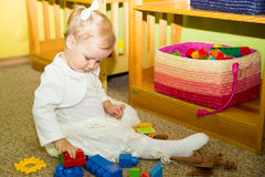 Little child girl playing in kindergarten in Montessori preschool Class. Adorable kid in nursery room. stock photos