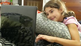 Little child girl playing in the notebook online game laptop stock video