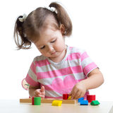 Little child girl playing with puzzle toys Stock Image