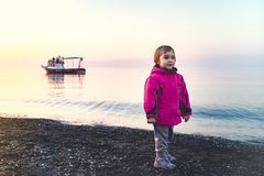 Little Child Girl Playing with Stones at Seaside in a Spring Season Evening. With Sunset light stock photography