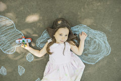 Little child girl plays astronaut. Little girl wearing a pilot hat with goggles holding in hand biplane toy laying down on asphalt after drawing clouds with Royalty Free Stock Photo