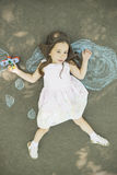 Little child girl plays astronaut. Little girl wearing a pilot hat with goggles holding in hand biplane toy laying down on asphalt after drawing clouds with Royalty Free Stock Photography