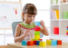 Little child girl playing with wooden colorful cubes in nursery room or kindergarten royalty free stock photo