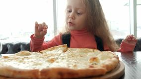 Little child girl portrait eat chew a piece of pizza Margarita in a pizzeria restaurant