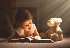 Little child girl is reading a book in evening in dark with a to. Y bear Royalty Free Stock Photos