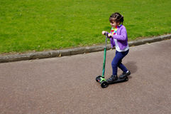 Little child girl ride a scooter Royalty Free Stock Image