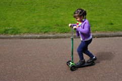 Little child girl ride a scooter Royalty Free Stock Photos