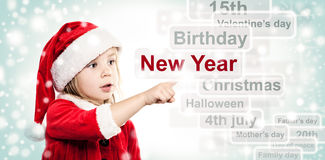 Little Child Girl in Santa Hat Pointing to New Year Royalty Free Stock Images