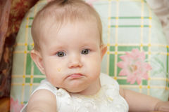 Little child girl sits in a highchair and eats cookies Stock Images