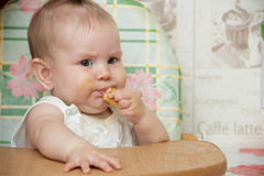 Little child girl sits in a highchair and eats cookies Stock Image