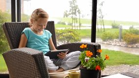 Little child girl sitting on the terrace in armchair with digital tablet stock footage